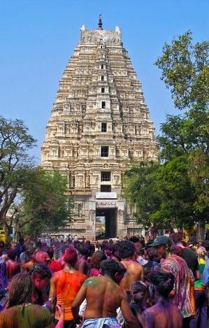 Holi revellers with Virupaksha Temple's gopuram in the background in the
