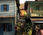 Green and blue timber shop houses beside the Mekong