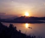 River boats slip across an orange Mekong