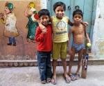 Boys playing cricket beside their doorway