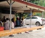 A monk performing a baci to bless a car at Wat Simuang