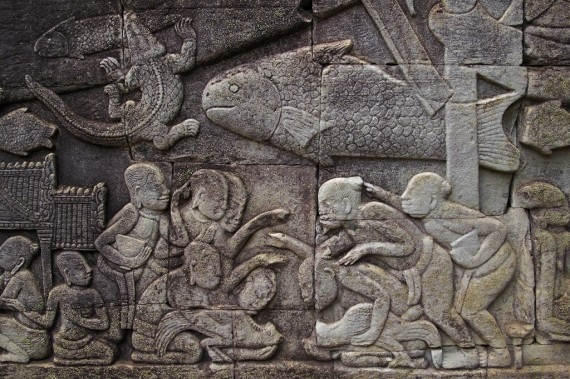 Groups of Chinese and Khmer prepare for a cockfight in a bas-relief at the Bayon