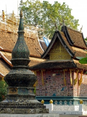 Scaffolding and a monk on the roof of Wat Xieng Thong