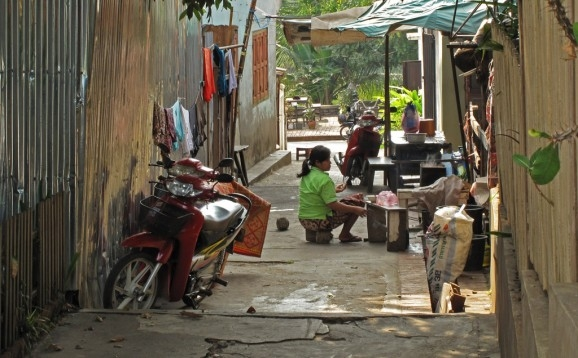A cat keeps a woman company in an historic district lane