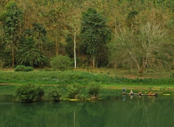 Fishermen float by on an green jade Nam Khan
