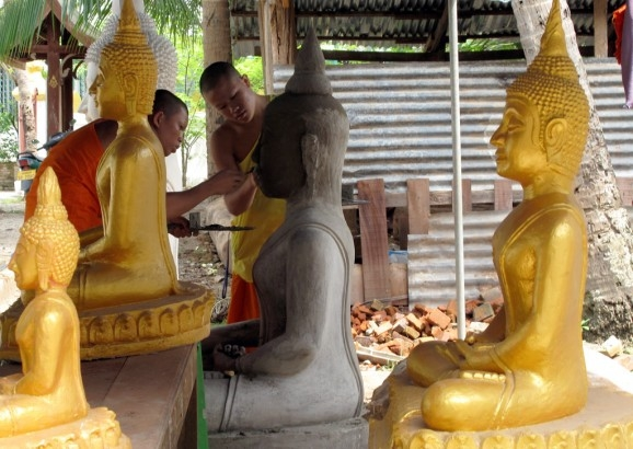 Monks work on a Buddha statue at a school dedicated to preserving traditional art forms