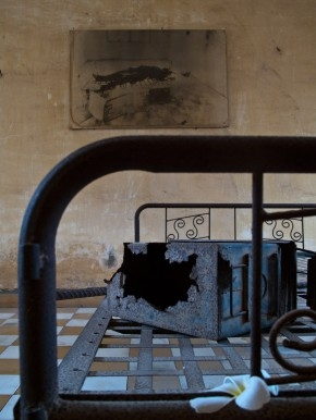 A cast-iron bed at Tuol Sleng, with the frangipani in the foreground and the photo of it in the background