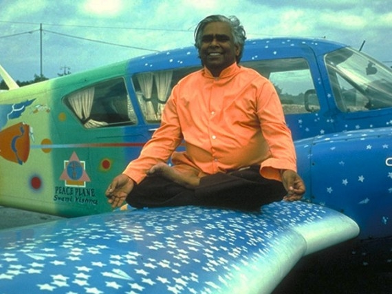 Swami Vishnu Devananda sitting in lotus position on his peace plane. He flew it over conflict zones, dropping flowers and chanting mantras for peace.