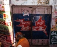 An Brahmin and a priah dog pass a door advertising Thums Up, India's spicy cola